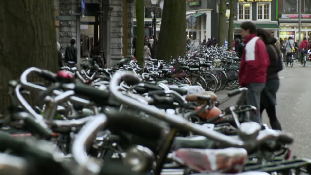 WS R/F View of line of bicycles tied up and people walking around / Amsterdam, Holland