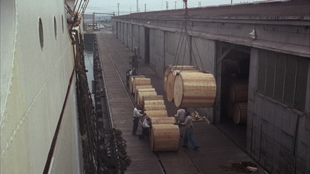 ms tu pan view of loading aboard ship  - stahlfass stock-videos und b-roll-filmmaterial