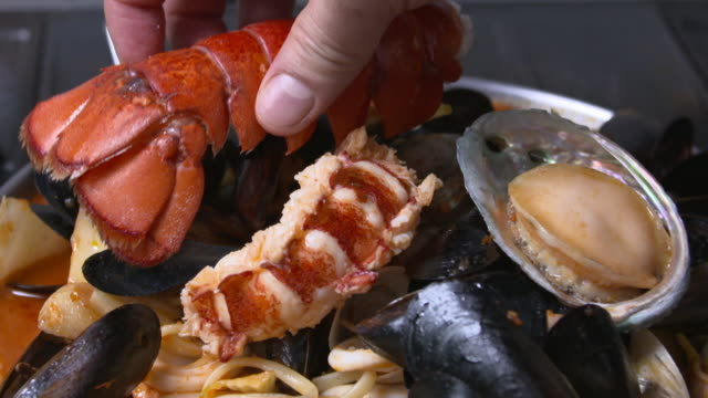 view of lobster shell being put on pecher pasta(seafood tomato stew with pasta) to decorate - clam seafood stock videos and b-roll footage