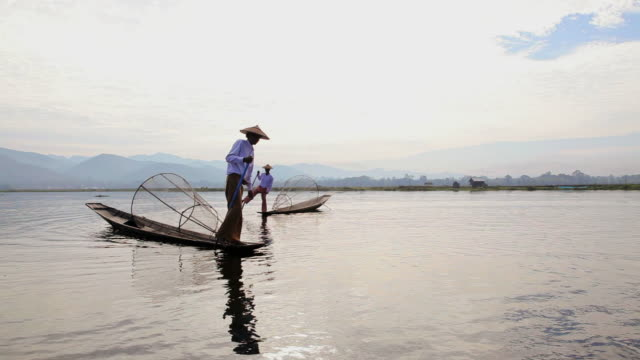WS View of Local leg rowing Intha Fishermen with conical net fishing on Inle Lake / Myanmar, Burma