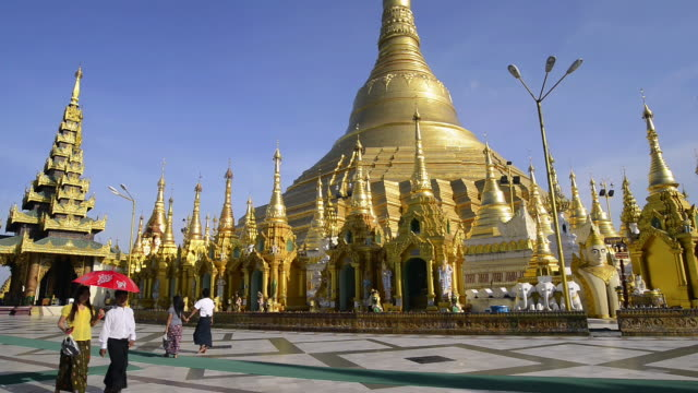 ws view of local people walking around golden stupa of famous shwedagon pagoda / yangon, yangon division, myanmar - pagoda stock videos and b-roll footage