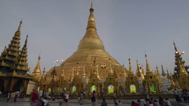ws view of local people walking around golden stupa of famous shwedagon pagoda at dusk / yangon, yangon division, myanmar - stupa stock videos & royalty-free footage