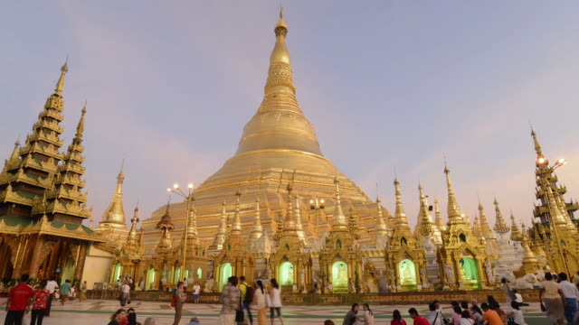 ws t/l view of local people walking around golden stupa of famous shwedagon pagoda, day to night / yangon, yangon division, myanmar - stupa stock videos & royalty-free footage