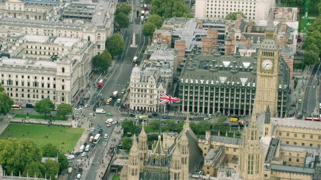 ws aerial pov view of london eye, big ben, thames river in cityscape / london, england, united kingdom - ビッグベン点の映像素材/bロール