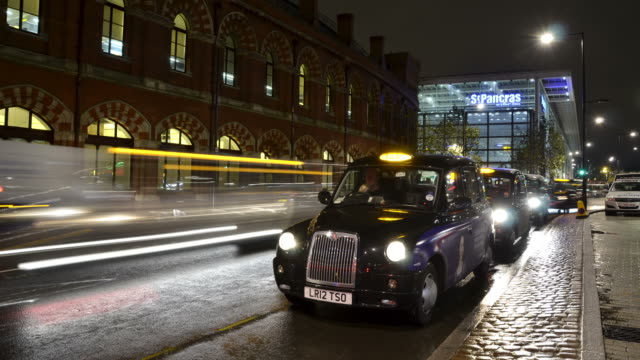 ws t/l view of london taxi cabs queuing outs kings cross station picking up passengers with st.pancras station at night / london, greater london, united kingdom - taxi stand stock videos and b-roll footage