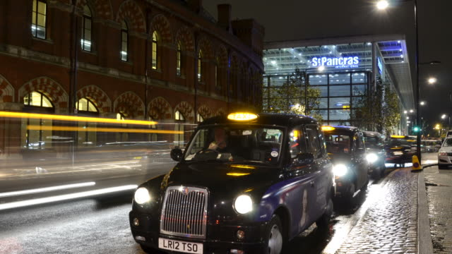 ws t/l zi view of london taxi cabs queuing outs kings cross station picking up passengers with st.pancras station at night / london, greater london, united kingdom - greater london stock videos & royalty-free footage