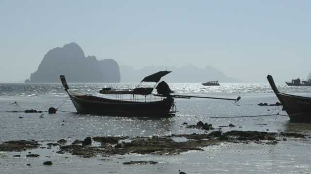 ws view of long tail boats and limestone rock in sea, marine national park / ko hai, krabi, thailand - 堆積岩点の映像素材/bロール