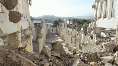 ws view of looking down on ruins of cathedral of our lady of assumption with rubble and mountains / port-au-prince, haiti - ハイチ点の映像素材/bロール