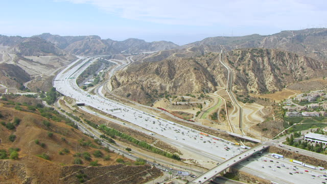 ws aerial pov view of los angeles aqueduct with traffic in foreground / los angeles, california, united states - lastzug stock-videos und b-roll-filmmaterial