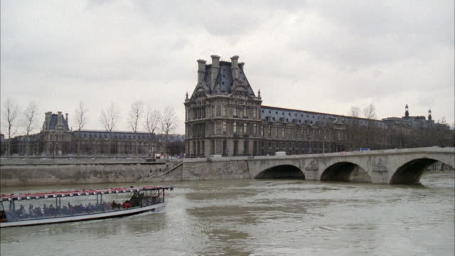 ws view of louvre building and boat traveling in river / paris, frace - warner bros stock videos & royalty-free footage