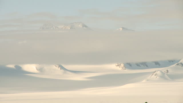 vídeos de stock, filmes e b-roll de ws view of low clouds moving across snowy mountain landscape / union glacier, heritage range, ellsworth mountains, antarctica  - pólo sul
