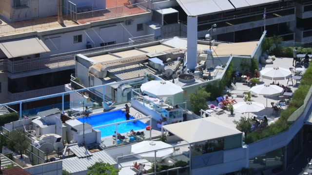 view of luxury hotel guests that enjoy a rooftop swimming pool pictured from the lycabettus hill on august 23 2020 in athens during the coronavirus... - lycabettus hill stock videos & royalty-free footage