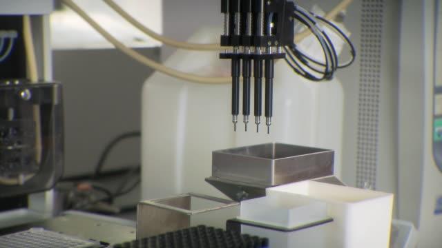 ms pov view of machines setting samples in lab / toronto, ontario, canada - campione medico video stock e b–roll