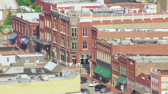 ws aerial view of main street in town with victorian brick buildings  / guthrie, oklahoma, united states - piccola cittadina video stock e b–roll