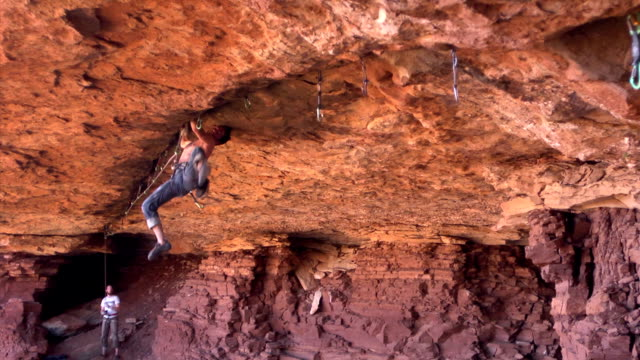 WS PAN ZI View of male climber climbing crack upside down / Moab, Utah, United States