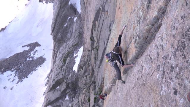 vidéos et rushes de ws zi view of male climber climbing rock with snow in backdrop / estes park, colorado, united states - un seul homme d'âge moyen