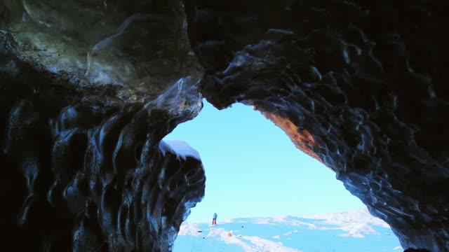 ws view of male figure walking nr glacier ice cave at svinaffellsjokull glacier, skaftafell / iceland - ice stock videos & royalty-free footage