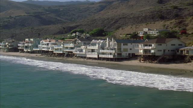 WS PAN View of Malibu coast along row of beachfront property of houses, homes, mansions / California, USA
