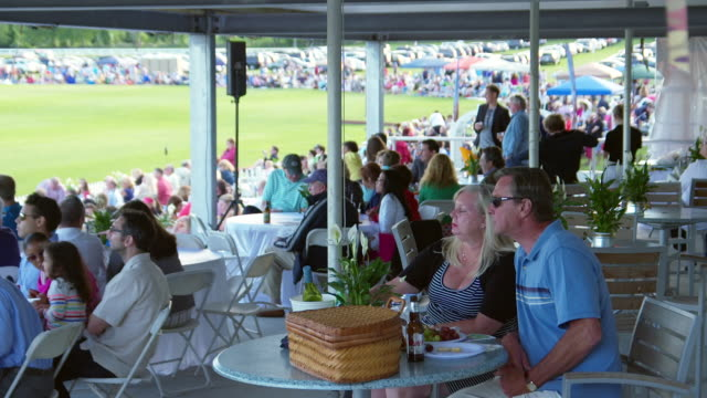 MS SLO MO View of man and woman eating while watching Newport Polo Competition / Portsmouth, Rhode Island, United States