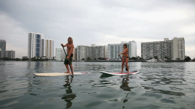 WS TS View of man and woman riding paddle boards in Miami harbor / Miami Beach, Florida, USA