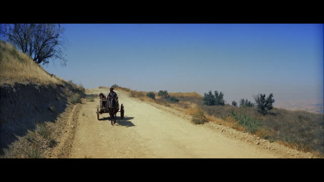 ws view of man and woman sitting in small cart - breitwandformat stock-videos und b-roll-filmmaterial