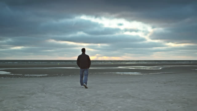 WS View of man at beach, walking towards sea / St. Peter Ording, Schleswig Holstein, Germany