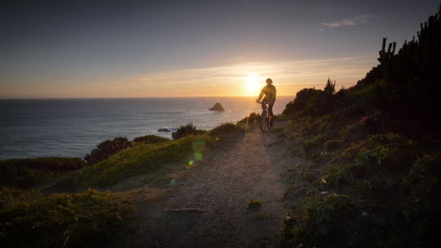 ws slo mo pov view of man bicycling on trail overlooking ocean / port orford heads state park, oregon, united states - oregon us state stock videos & royalty-free footage