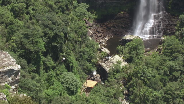 vídeos y material grabado en eventos de stock de ws aerial ts view of man bungee jumping in front of waterfall / nelspruit, mpumalanga, south africa - puenting