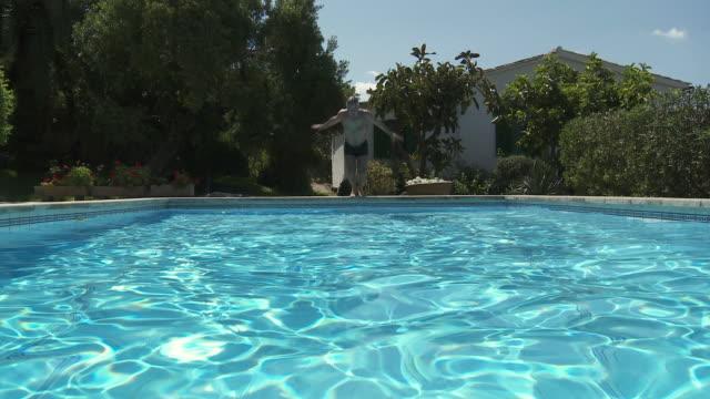 ms view of man diving in swimming pool / palma de majorque, majorque, spain - utebassäng bildbanksvideor och videomaterial från bakom kulisserna