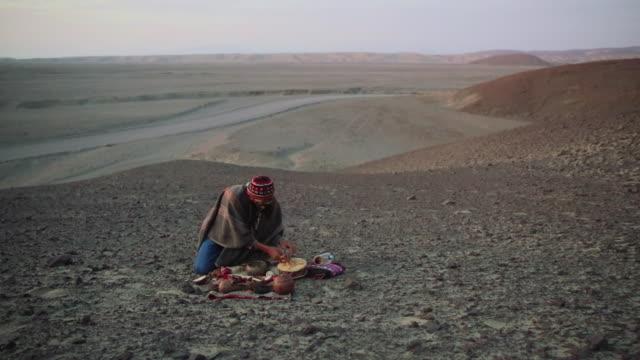 vídeos y material grabado en eventos de stock de ws view of man doing native ritual audio / south of peru, nazca, peru - un solo hombre de mediana edad