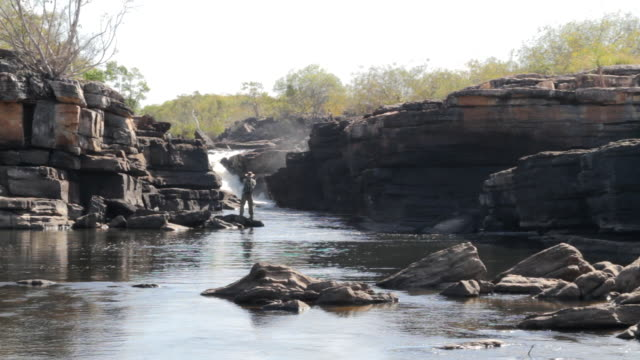 MS View of Man fishing at small waterfall in river/ Northern Territory, Australia