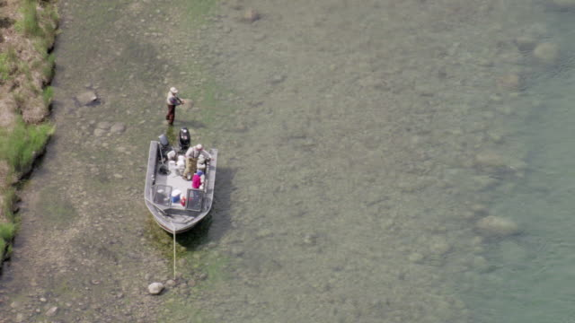 MS AERIAL View of man fishing for sockeye salmon in Naknek river while people sit in boat / Alaska, United States