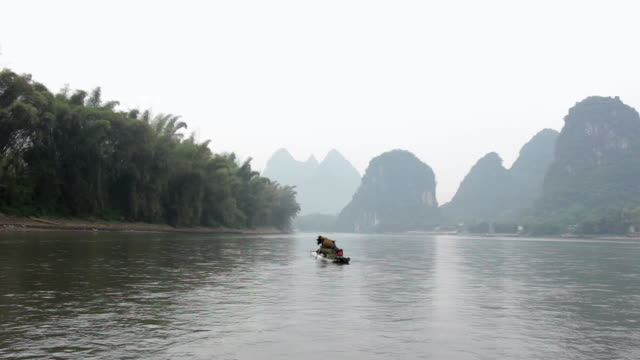 ws view of man fishing with birds and river surroundings / close to li river, guangxi, china - li river stock videos & royalty-free footage