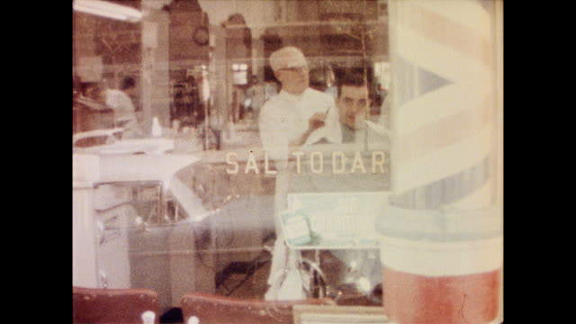 vidéos et rushes de view of man getting hair cut by barber as seen through the front window of the store / rotating barber's pole off to the side men at the barbershop... - barber shop