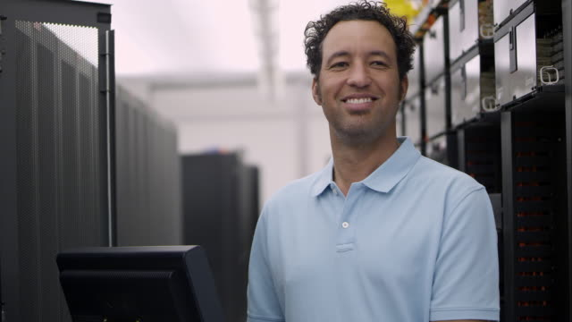 view of man in server room smiling - polo shirt stock videos & royalty-free footage