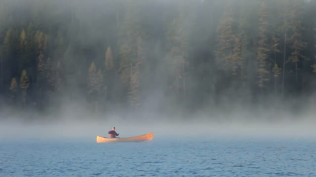 WS View of Man in wood cedar strip canoe fly fishing on calm, misty, foggy mountain lake with sunrise lighting up canoe / Sealy Lake, Montana, United States