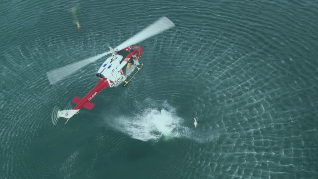 WS AERIAL ZI View of man jumping from rescue helicopter into sea / Cape Town, Western Cape, South Africa