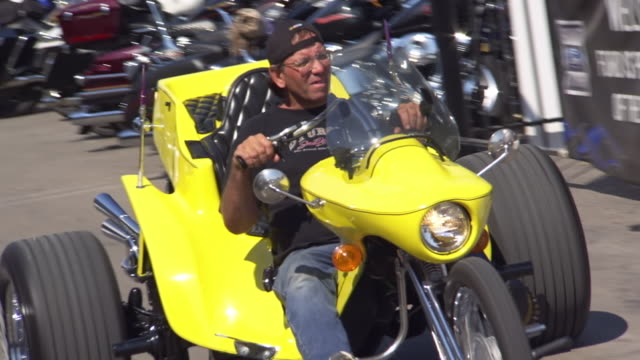 WS TS View of man on yellow three wheeler motorcycle riding down main street during Sturgis Motorcycle Rally / Sturgis, South Dakota, United States