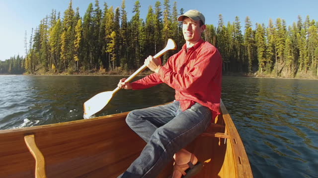 vídeos de stock, filmes e b-roll de ms pov view of man paddling cedar strip canoe on misty mountain lake / sealy lake, montana, united states - só um homem jovem
