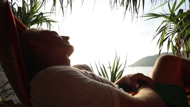 view of man relaxing in hammock - lying on back stock videos & royalty-free footage