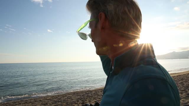 vidéos et rushes de cu pov view of man relaxing on beach, at sunrise - seulement des hommes d'âge mûr
