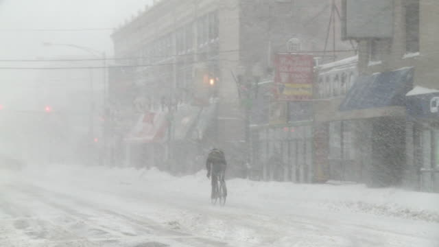 WS PAN View of man riding bicycle in snow storm / Chicago, Illinois, USA
