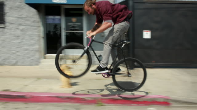 ws ts view of man riding bike, jumping curbs, on city street / los angeles, california, united states - pavement video stock e b–roll