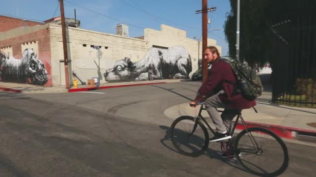 vidéos et rushes de ws slo mo ts view of man riding bike on city street in / los angeles california united states - un seul homme d'âge moyen