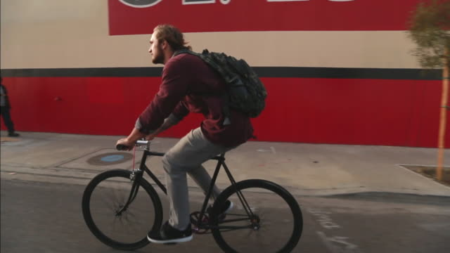 vídeos de stock e filmes b-roll de ws slo mo ts view of man riding bike on city street / los angeles california united states - vida urbana