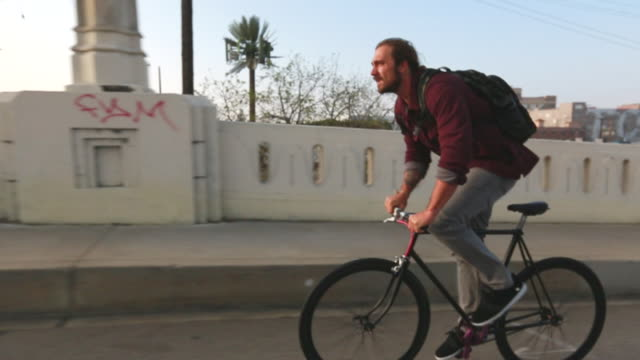 ws slo mo ts view of man riding bike on city street / los angeles california united states - radfahren stock-videos und b-roll-filmmaterial