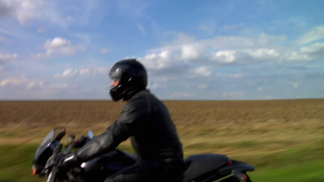 MS TS View of man riding motorbike on country road / London, UK