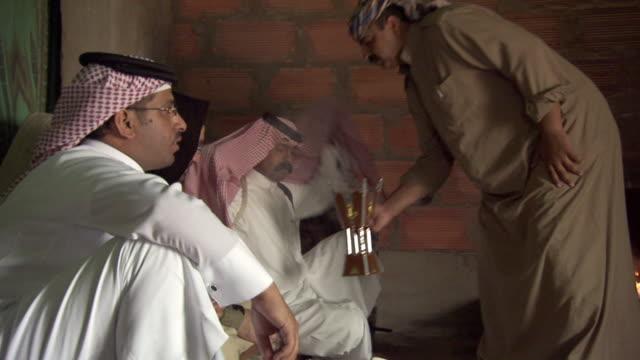MS View of man serving buhkhoor / Najran City, Najran, Saudi Arabia