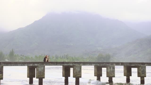 stockvideo's en b-roll-footage met ws view of man sitting on dock looking out through his binoculars near mountain / oahu, hawaii, united states - wiese