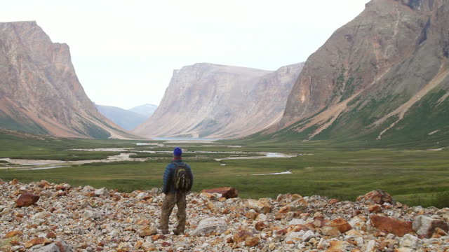 ws pan view of man standing on rocky stones with mountains and valley / torgat mtns, labrador, canada - wiese stock videos & royalty-free footage